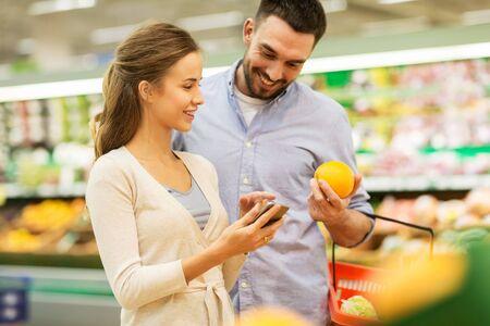 Paare mit kaufenden Orangen des Smartphone am Lebensmittelgeschäft