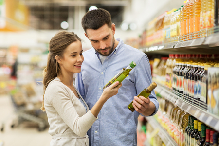 happy couple buying olive oil at grocery store Stockfoto