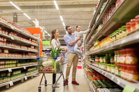 family with food in shopping cart at grocery store Фото со стока - 69547088