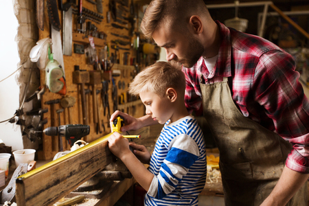 father and son with ruler measure wood at workshop Stok Fotoğraf - 69511324
