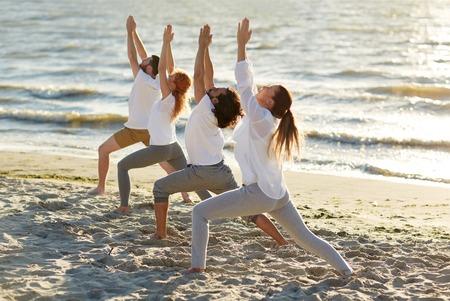 해변에서 요가 연습을 만드는 사람들의 그룹