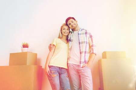 on the move: smiling couple with big boxes moving to new home Stock Photo