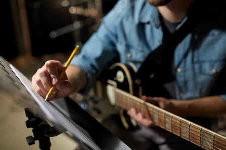melodist: man with guitar writing to music book at studio