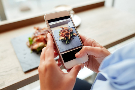 appetizers: hands with smartphone photographing food