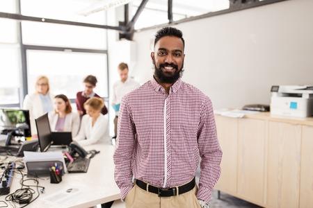 Glücklicher indischer Mann über Kreativ-Team im Büro Standard-Bild - 69511800