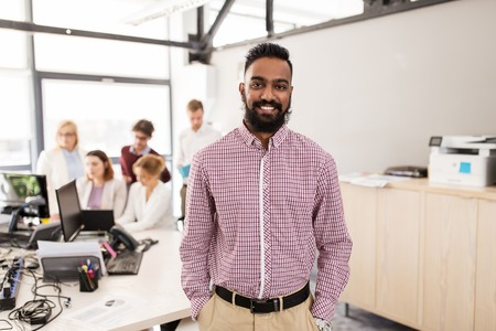 happy indian man over creative team in office