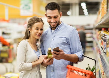 식료품 점에서 올리브 오일을 사는 스마트 폰과 커플