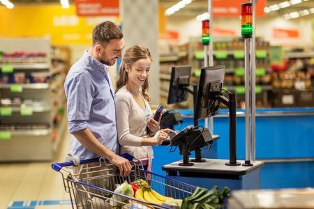 현금 등록기에서 식료품 점에서 음식을 사는 부부 스톡 콘텐츠