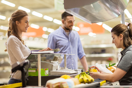 happy customer: couple buying food at grocery store cash register Stock Photo