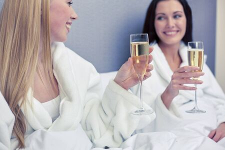 bathrobes: happy women in bathrobes with champagne glasses