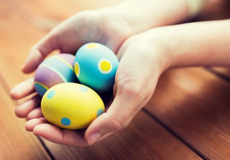 hand colored: close up of woman hands with colored easter eggs