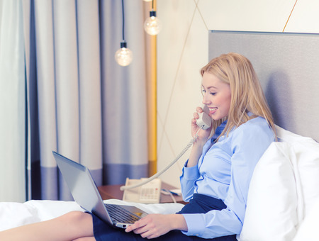 businesswoman with laptop and phone in hotel room
