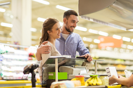 supermarket cash: shopping, sale, consumerism and people concept - happy couple buying food at grocery store or supermarket cash register Stock Photo