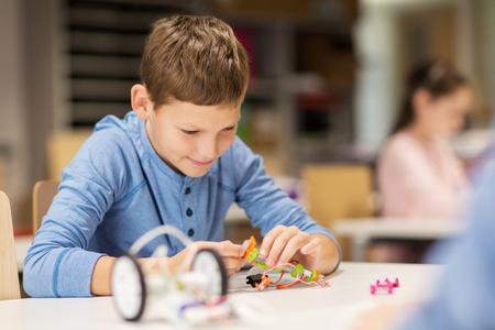 Onderwijs, kinderen, technologie, wetenschap en mensenconcept - close-up van jongensbouwrobot bij robotica schoolles Stockfoto