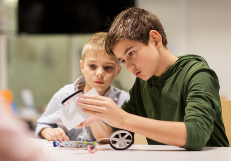 education, children, technology, science and people concept - happy boys building robots at robotics school lesson