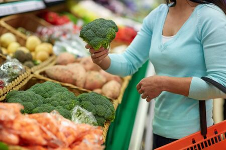 purchaser: woman with basket buying broccoli at grocery store Stock Photo