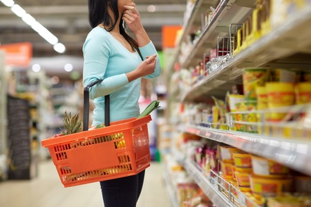 food basket: sale, shopping, consumerism and people concept - woman with food basket at grocery store or supermarket