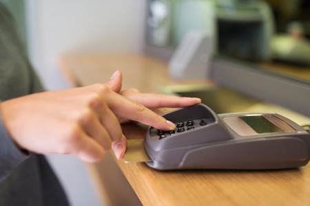 operating key: finance, money, technology, payment and people concept - close up of hand entering pin code to card reader terminal