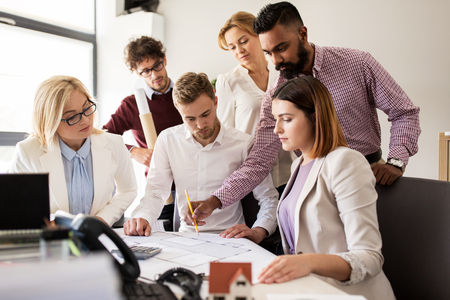 building estate: building, construction, architecture, real estate and people concept - business team with blueprint meeting and discussing house project at office Stock Photo