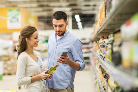 shopping, food, sale, consumerism and people concept - happy couple with smartphone buying olive oil at grocery store or supermarket Stok Fotoğraf