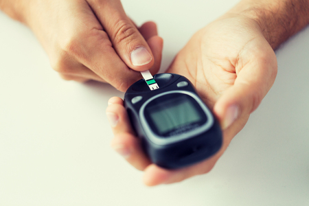 hyperglycemia: medicine, diabetes, glycemia, health care and people concept - close up of man checking blood sugar level by glucometer and test stripe at home
