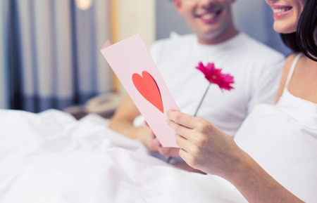 enamorados en la cama: love, relationships, holidays, valentines day and people concept - close up of happy couple in bed with postcard and flower