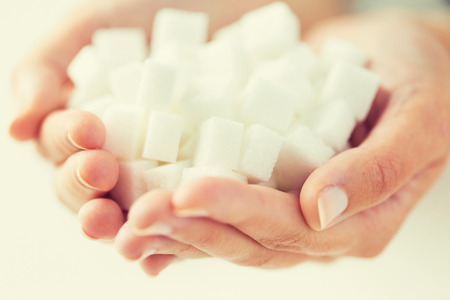hyperglycemia: food, junk-food, diabetes and unhealthy eating concept - close up of white lump sugar in woman hands