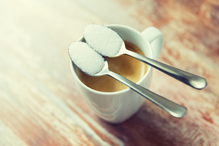 hyperglycemia: junk-food, diabetes and unhealthy eating concept - close up of white sugar on teaspoon and coffee cup