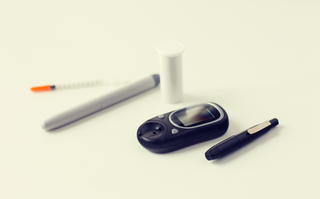 glycemic: medicine, diabetes, medical tool and health care concept - close up of glucometer, insulin pen and syringe on table