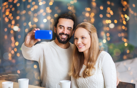 happy couple with tablet pc and coffee at cafe