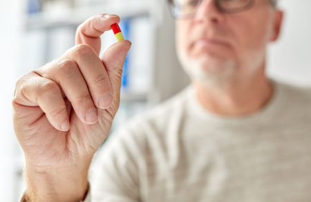 close up of old man hand with pill Stock Photo