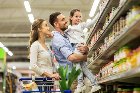 食料品店でショッピング カートに食物と一緒に家族