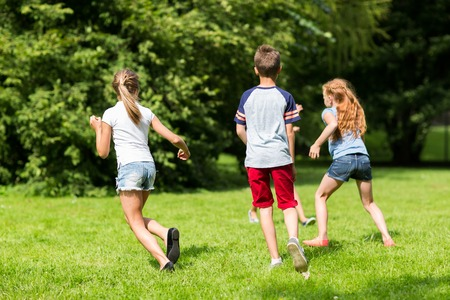 group of happy kids or friends playing outdoors Zdjęcie Seryjne