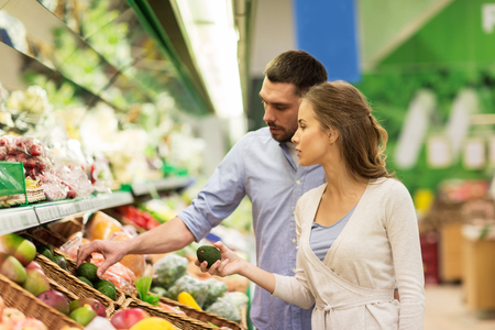 happy couple buying avocado at grocery store Stock Photo