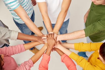 skupina mezinárodních lidí s rukama společně
