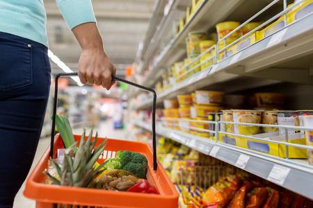 Frau mit Nahrungsmittelkorb im Supermarkt oder Supermarkt
