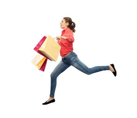 personas corriendo: sonriente mujer joven con bolsas de la compra de saltar