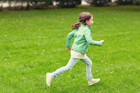 summer, childhood, leisure and people concept - happy little girl running on green summer field Stock Photo