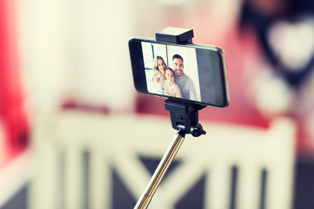 extensible: technology and people concept - close up of happy family picture on smartphone screen with selfie stick