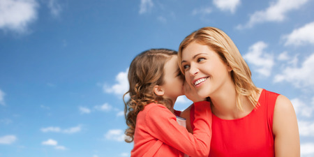 people, family and communication concept - happy mother and daughter whispering something into ear over blue sky background