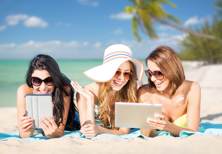travel background: summer holidays, technology, people, travel and internet concept - happy young women in bikinis with tablet pc computers sunbathing over exotic tropical beach with palm trees and sea shore background