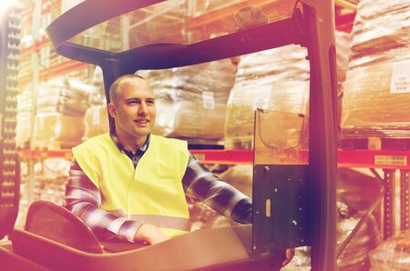 smiling man operating forklift loader at warehouse Stock Photo
