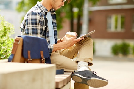 creative communication: business, education, technology, communication and people concept - close up of creative or hipster man with tablet pc computer drinking coffee from paper cup and sitting on city street bench Stock Photo