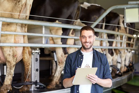 agriculture industrial: agriculture industry, farming, people, milking and animal husbandry concept - young man or farmer with clipboard and cows at rotary parlour system on dairy farm
