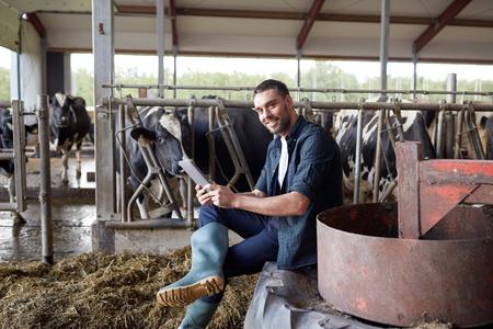 농업 산업, 농업, 사람, 기술 및 축산 개념 - 젊은 남자 또는 농부와 tablet pc 컴퓨터 및 낙농 농장에서 암소에 소