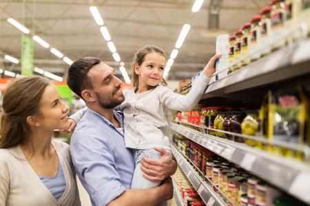 Vendita, acquisto, consumismo e concetto della gente - famiglia felice con il bambino che compra alimento alla drogheria o al supermercato Archivio Fotografico - 70247130