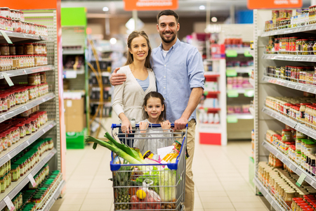 sale, consumerism and people concept - happy family with child and shopping cart buying food at grocery store or supermarket Stok Fotoğraf
