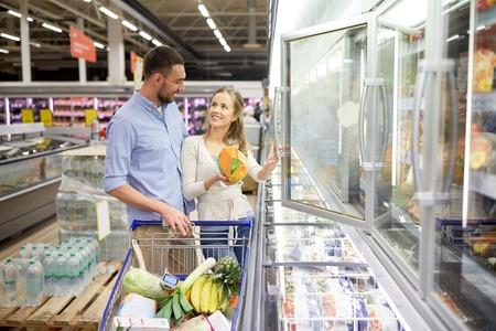 alimentos congelados: Pares con el carrito de compra de comida en la tienda de comestibles Foto de archivo