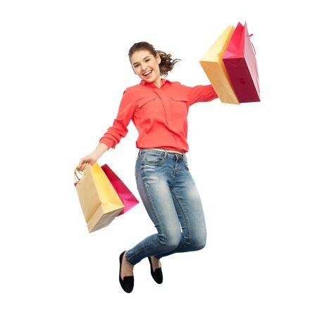 ジャンプの買い物袋を持つ笑顔の若い女性