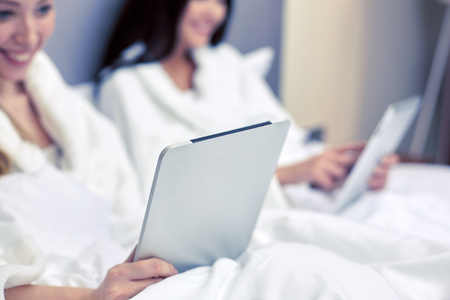 bathrobes: happy women in bathrobes with tablet pc at hotel